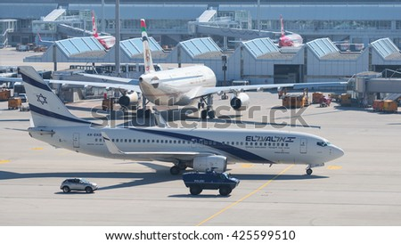 Munich, Germany - May 6, 2016: Aircraft Boeing 737-800 by Israeli airline El Al taxiing to airport terminal with escort armored vehicle ensures antiterrorism force protection  - stock photo