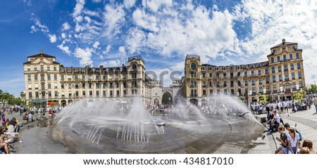 Munich, Germany - MAY 27, 2016: People walking along through the Karlstor gate in Munich and refresh at the water fountain. - stock photo