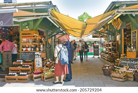 MUNICH, GERMANY - MAY 24,2014. Viktualien Markt open air market in Munich center is a shopping landmark that offers daily gourmet delicacies and wines to regular visitors and tourists - stock photo