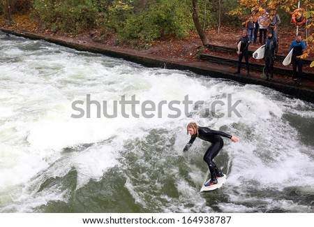 MUNICH, GERMANY - NOVEMBER 1: Surfers train on a man-made wave about 1 metre high in the Eisbach river in English Garden on November 1, 2013 in Munich, Germany.