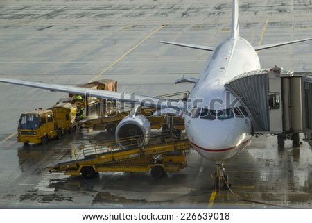Munich, Germany - October 16: Ground crew refueling and working below a passenger airplane in Munich on October 16, 2014.Munich, Germany - stock photo