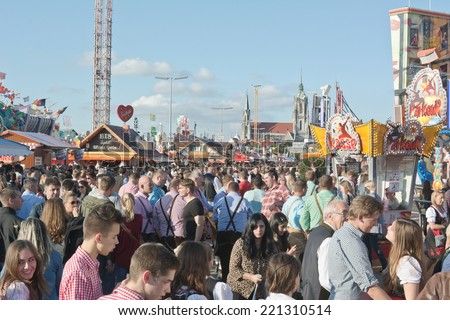 MUNICH, GERMANY - SEPT. 27, 2014: Crowds of visitors at the Oktoberfest celebrating the festivities. The Festival runs from Sept. 20 - Oct. 5  in Munich, Germany - stock photo
