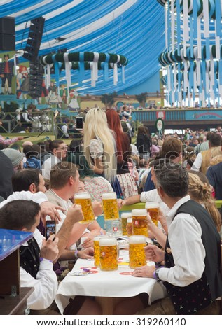 MUNICH, GERMANY - SEPT. 19, 2015:  Oktoberfest Crowds of visitors at the Spatenbrau Tent celebrating the festivities. The Festival runs from September 19th until October 4th 2015 in Munich, Germany