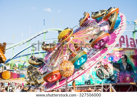 MUNICH, GERMANY - SEPTEMBER 30: Fairground rides at Oktoberfest in Munich, Germany on September 30, 2015. Oktoberfest is the biggest beer festival of the world with over 6 million visitors each year.  - stock photo