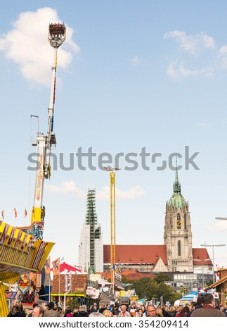 MUNICH, GERMANY - SEPTEMBER 30: Fairground rides at the Oktoberfest in Munich, Germany on September 30, 2015. Oktoberfest is the biggest beer festival of the world with over 6 million visitors a year - stock photo