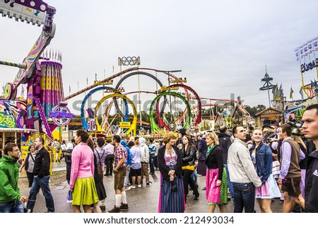 MUNICH, GERMANY - SEPTEMBER 22, 2012: Oktoberfest Munich: People are walking , partly dressed in traditional costumes. In the background are colorful fairground attractions. - stock photo