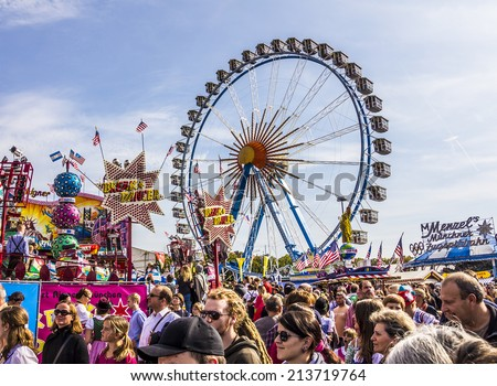 MUNICH, GERMANY - SEPTEMBER 23, 2012: Oktoberfest Munich: The big Ferris wheel. In the foreground people are walking between beer tents and fairground attractions. - stock photo