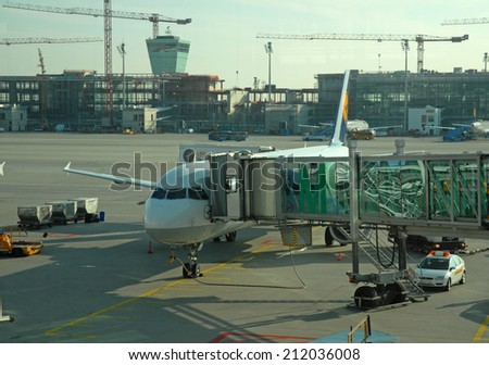 MUNICH, GERMANY-SEPTEMBER 25, 2013: passengers airplane decking. With 38 millions passengers per year it is one of the most important airport in Europe. - stock photo