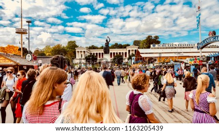 MUNICH/ GERMANY - SEPTEMBER 2017: people dressed for the Oktoberfest walking around. In the background the Bavaria statue - symbol of the Bavaria State - overlooking the beer festival.