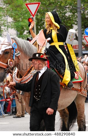 Munich,Germany- September 19th, 2015:Woman dressed as the Munich Kindl waves during the brewers' parade of the 2015 Oktoberfest