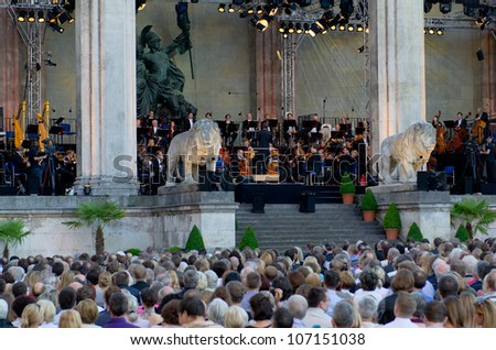 MUNICH - JULY 7: Juraj Valcuha, Conductor, with the Munich philharmonic orchestra at the open-air classic festival classic at the Odeonsplatz square in Munich on July 7, 2012. - stock photo