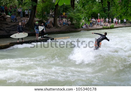 MUNICH - JUNE 16: The Eisbach (German for ice brook), located in the park Englischer Garten, forms a standing wave, which is a popular river surfing spot in Munich, Germany on June 16, 2012. - stock photo