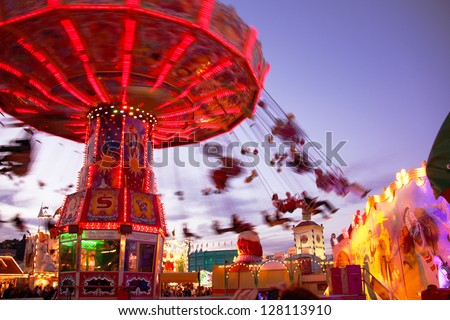 MUNICH - OCTOBER 4: An illuminated chairoplane is attracting visitors at the Oktoberfest fair ground in Munich on October 4, 2010 in Munich, Germany. - stock photo