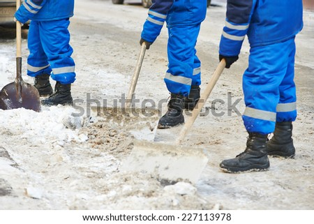 municipal urban servicing workers shoveling snow during winter road cleaning  - stock photo