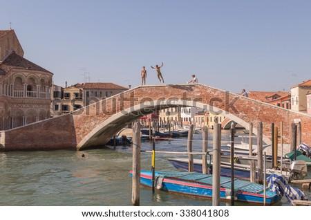 Murano - August 5: kids jumping bridge in Venice Murano in Venice Italy, August 5, 2015. - stock photo