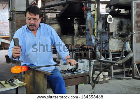 MURANO ISLAND - MAY 01 2011:Glassblowing artisan at work in a crystal glass workshop in Murano island Venice Italy.Murano glassmakers use the same tools as their ancestors have thousands of years ago - stock photo
