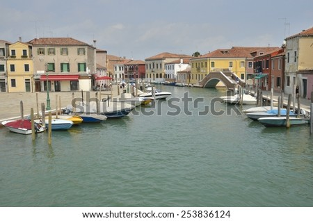 MURANO, ITALY -AUGUST 10: Beautiful canal with boats parked along the canal on August 10, 2014 in Murano, an island of Venice, Italy - stock photo