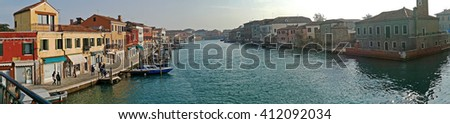 MURANO, ITALY - JANUARY 25, 2016: Panorama in Venice, Italy, Murano. Water boats canal and traditional buildings.117 islands separated by canals and bridges. Murano is glass making island.  - stock photo