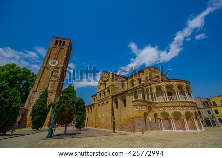 MURANO, ITALY - JUNE 16, 2015:  Spectacular view in a sunny day of Murano s Cathedral, Santa Maria e San Donato with the clock tower.  - stock photo