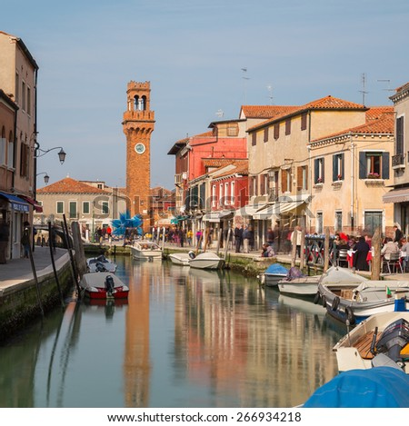 MURANO, ITALY - 14TH MARCH 2015: A view along streets in Murano with the bell tower in the background. People can be seen along the paths. - stock photo