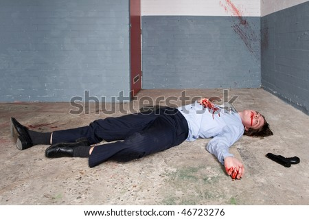 Murdered businessman lying on the floor of a basement, the gun next to the dead body - stock photo