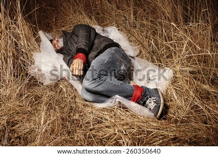 Murdered man left in winter grass by criminal after hitch-hiking - stock photo