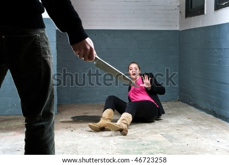 Murderer, holding a knife, face to face with a terrified woman in a basement