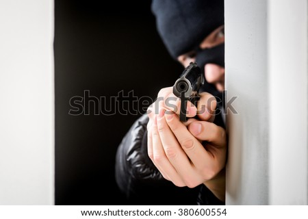 Murderer in a mask with an aiming black gun - stock photo