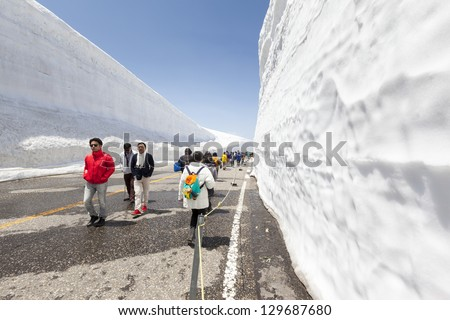 "MURODO, JAPAN - MAY 16: Tourists at the ""Yuki-no-Ohtani"" valley of snow in Murodo, Japan on 16th May 2012. Every spring the deep snow is cleared from the road leaving steep snow walls up to 18m high."