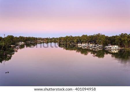 Murray river bend near Mildura with calm and still flow of water at sunrise. Residential and fishing floating houses docked to Victorian and NSW sides of the river. - stock photo