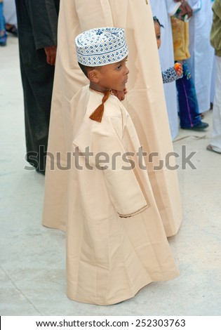 MUSCAT, OMAN - FEBRUARY 1, 2008: A young Omani boy, immaculately dressed in traditional clothing, holds on to his father's hand in Muscat in the Sultanate of Oman.