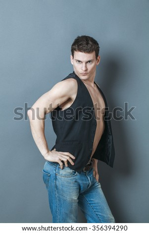 muscle concept - arrogant young man posing in showing his bodybuilding muscles and body,studio shot,low contrast effect