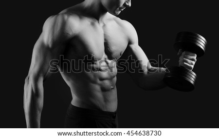 Muscle definition. Cropped monochrome shot of a male bodybuilder working out shirtless showing off his hot ripped muscular body - stock photo