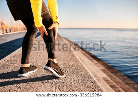 Muscle injury - Athlete running clutching calf muscle after spraining it while out jogging on the beach near ocean. Sports injury concept with running man outside