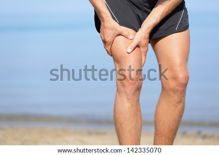 Muscle injury. Man with sprain thigh muscles. Athlete in sports shorts clutching his thigh muscles after pulling or straining them while jogging on the beach. - stock photo