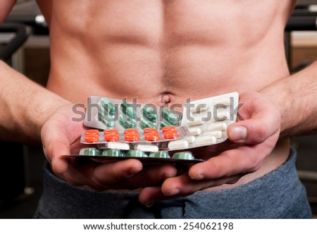 Muscle man holding bunch of blisters with colored vitamin pills - stock photo