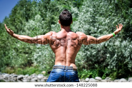 Muscle man in jeans, outdoor with arms spread open, seen from the back, muscular shoulders - stock photo
