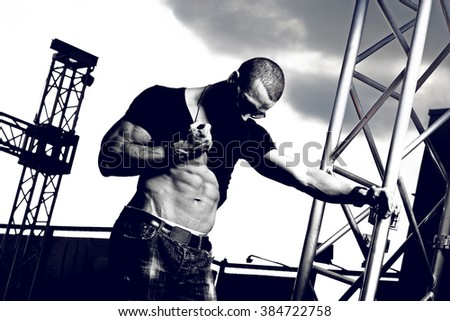 Muscle man in jeans posing autdoor. Fashion photo. - stock photo