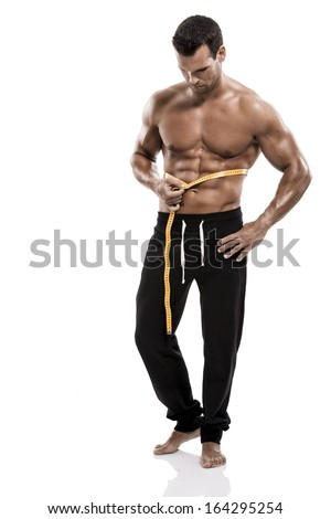Muscle man in studio taking is measures, isolated over a white background - stock photo