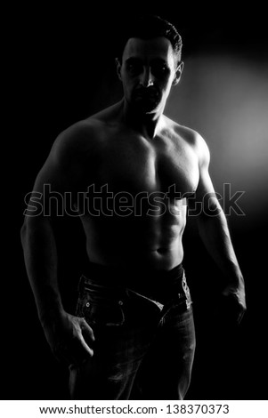 muscle man posing in studio, black and white,black background