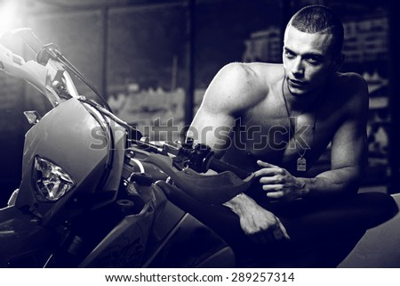 Muscle man seat on the motorcycle outdoor .Fashionable photo.
