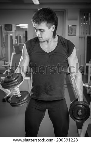 Muscle man with dumbbells.Black and white