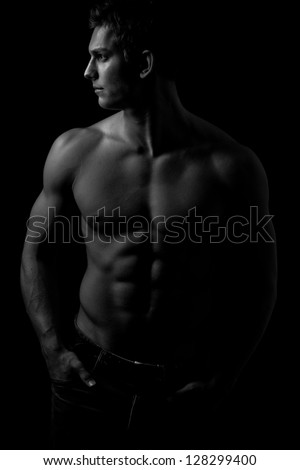 Muscle sexy naked young man with perfect body, low key - stock photo