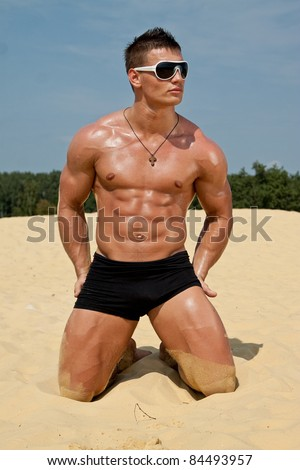Muscle sexy wet naked young man posing on the beach - stock photo