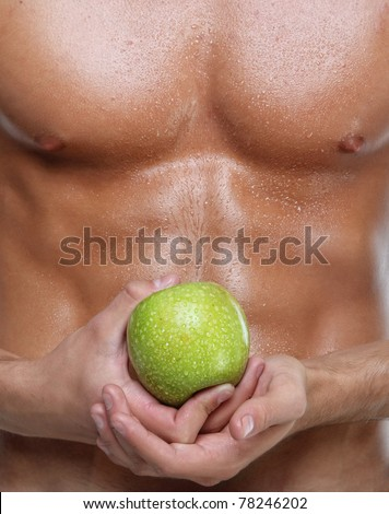Muscle sexy wet naked young man torso and green apple in hands