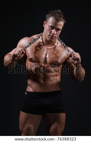Muscle sexy wet nude young man posing in trunks with chain in hands