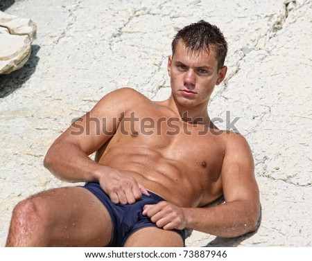 Muscle wet sexy naked man lying on rock outdoors