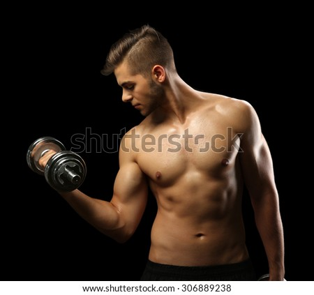 Muscle young man holding dumbbell on dark background - stock photo