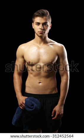 Muscle young man holding towel on dark background - stock photo