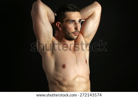 Muscle young man on black background